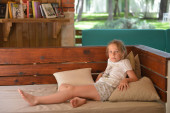 fiatal lány pihenés egy nagy padon szabadtéri trópusi park