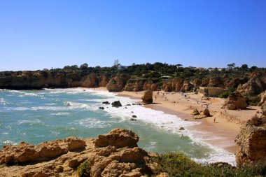 Wonderful view of the beautiful Praia Rafael in south Portugal. People and families enjoying the one of the most spectacular beaches in Albufeira, Algarve region.