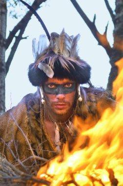 Genç bir şaman büyücünün portresi. Kürk, tüy ve hayvan kemikleri içinde. Parlak bir ateşin yanında.