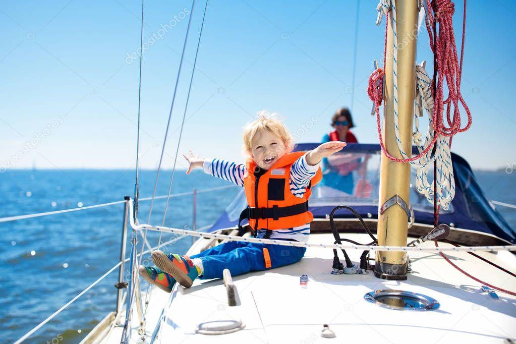 I bambini salpano in barca in mare. Bambino che naviga in barca. Un ragazzino con giubbotti salvagente viaggia su una nave oceanica. Ai bambini piace la crociera in barca. Vacanze estive per la famiglia. Giovane marinaio sul ponte anteriore barca a vela.