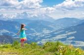 Fotografie Kinder Wandern in den Alpen. Kinder Blick auf Schnee bedeckt Berg Österreichs. Frühling Urlaub mit der Familie. Kleines Mädchen auf Wanderung Trail in blühenden Almwiese. Outdoor-Spaß und gesunde Bewegung