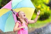 Fotografie Kinder spielen im Regen. Kinder mit Regenschirm spielen im Freien bei starkem Regen. Kleines Mädchen im ersten Frühjahr Dusche gefangen. Kinder outdoor-Spaß von regnerischen Herbstwetter. Kind im tropischen Sturm laufen