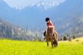 Děti, jezdící poník v pohoří Alp. Rodinné jarní prázdniny na ranči koně v Rakousku, Tyrolsko. Děti jezdit na koni. Chlapče, starat se o zvíře. Dítě a zvíře. Malá holčička v kvetoucí louka