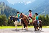 Děti, jezdící poník v pohoří Alp. Rodinné jarní prázdniny na ranči koně v Rakousku, Tyrolsko. Děti jezdit na koni. Chlapče, starat se o zvíře. Dítě a zvíře. Malou holčičku a chlapce v sedlo na poníka
