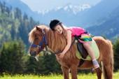 Děti, jezdící poník v pohoří Alp. Rodinné jarní prázdniny na ranči koně v Rakousku, Tyrolsko. Děti jezdit na koni. Chlapče, starat se o zvíře. Dítě a zvíře. Malá holčička v kvetoucí louka.