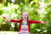 Fotografie Niedliche kleine Mädchen mit großen bunten Lollipop. Kind, essen Süßigkeiten Bar. Süßigkeiten für kleine Kinder. Sommer-outdoor-Spaß. Vorschulkind Kind mit Zucker am Stiel. Kinder mit Imbiss in einem Park nach der Vorschule