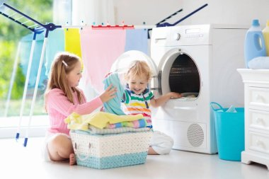 Children in laundry room with washing machine or tumble dryer. Kids help with family chores. Modern household devices and washing detergent in white sunny home. Clean washed clothes on drying rack.