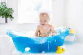 Fotografie Glücklich lachende Baby ein Bad mit Schaum Blasen spielen zu nehmen. Kleines Kind in einer Badewanne. Kind im Bad mit bunten Spielzeug Ente lächelnd. Baby waschen und Baden. Hygiene und Pflege für Kleinkinder
