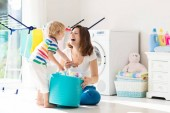 Fotografie Mother and kids in laundry room with washing machine or tumble dryer. Family chores. Modern household devices and washing detergent in white sunny home. Clean washed clothes on drying rack.