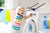 Fotografie Child in laundry room with washing machine or tumble dryer. Kid helping with family chores. Modern household devices and washing detergent in white sunny home. Clean washed clothes on drying rack.
