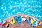 Fotografie Swimming pool accessories flat lay. Top view of beach items on pool deck. Flip flops, bikini and hat, sun glasses. Water toys. Summer vacation in tropical resort. Copy space. Colorful beach wear.