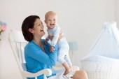 Fotografie Junge Mutter hält ihr neugeborenes Kind. Mama Pflege Baby. Frau und Neugeborene Junge im weißen Schlafzimmer mit Schaukelstuhl und blau Krippe. Kindergarten-Innenraum. Mutter mit Kind lachen spielen. Familie zu Hause