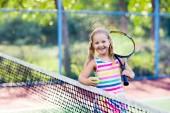 Dítě hrající tenis na venkovním hřišti. Holčička s tenisovou raketu a míček v sportovního klubu. Aktivní cvičení pro děti. Letní aktivity pro děti. Školení pro mladé dítě. Dítě učí hrát