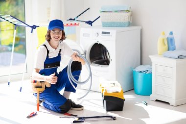 Washing machine repair service. Young male technician in blue uniform examining and repairing broken washer or tumble dryer. Maintenance of home and household appliance. Plumber apprentice at work.
