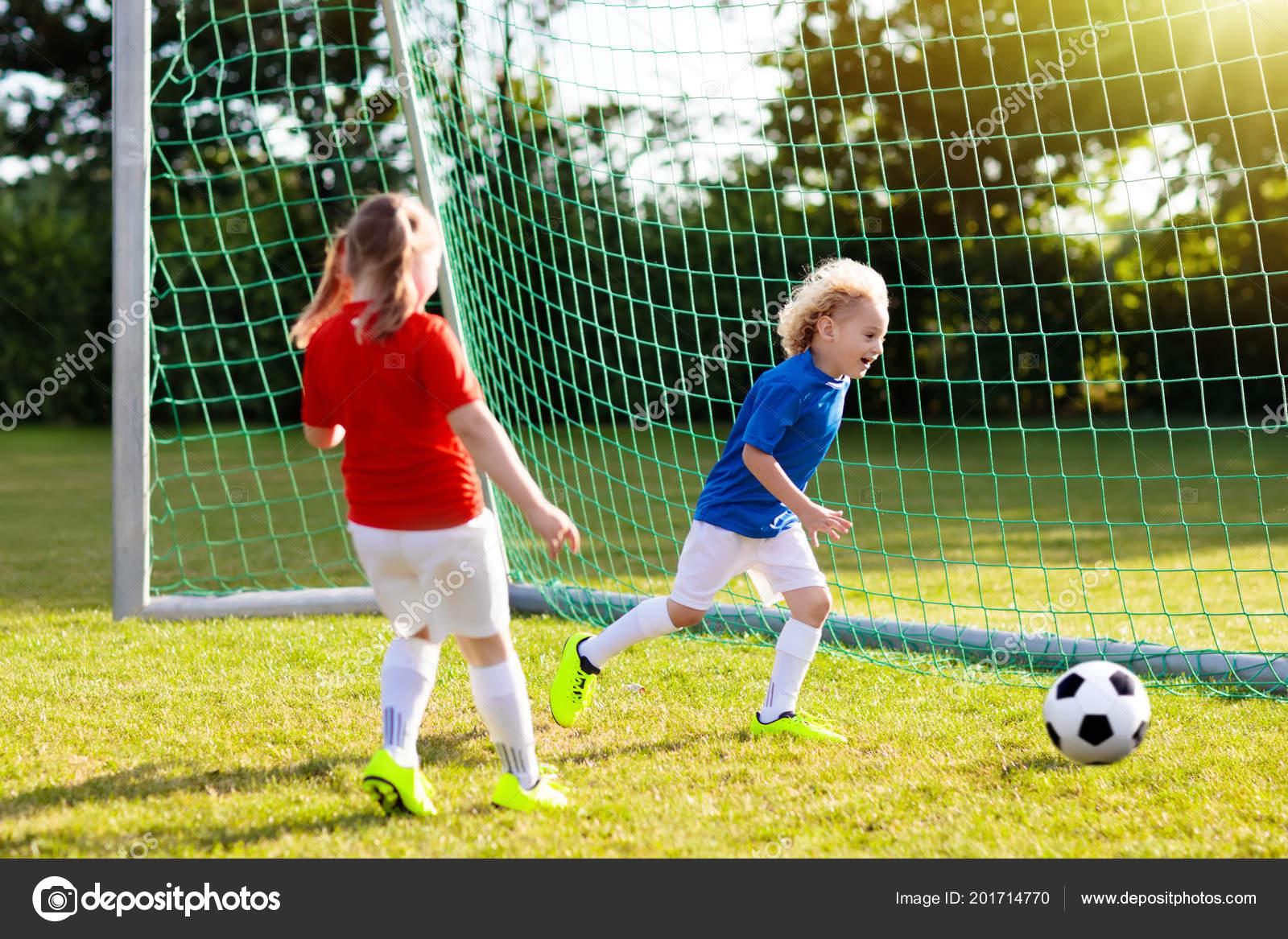 Los niños jugar al fútbol en el campo al aire libre. Los niños anotar un gol  en el partido de fútbol. Niña y niño pateando pelota. Niño corriendo en  Maillot ... 6a60b7519d72f