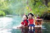 Fotografie Děti oblečené v pirátské kostýmy a klobouky s truhla s pokladem, dalekohledy mohli lidé pokládat a meče na dřevěné pramici plachtění v řece v horkém letním dni. Roli piráti hra pro děti. Vodní zábava pro rodinu