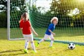 Děti hrají fotbal na venkovním hřišti. Děti gól na fotbal. Dívka a chlapec kope míč. Běžící dítě v týmu dres a kopačky. Školní fotbalový klub. Sportovní výcvik pro mladé hráče
