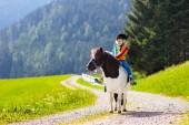 Děti, jezdící poník v pohoří Alp. Rodinné jarní prázdniny na ranči koně v Rakousku, Tyrolsko. Děti jezdit na koni. Chlapče, starat se o zvíře. Dítě a zvíře. Chlapeček v sedlo na poníka