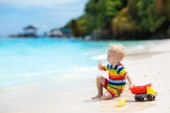 Fotografie Child playing on tropical beach. Little boy digging sand at sea shore. Family summer vacation. Kids play with water and sand toys. Ocean and island fun. Travel with young children. Asia holiday.