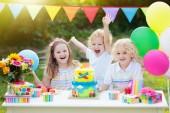 Fotografie Kinder Schlag Kerzen auf der Geburtstagstorte. Kids party Dekoration und Essen. Jungen und Mädchen feiert Geburtstag von Little Brother. Transport und Auto Kind Veranstaltung Thema. Kind mit Geschenken und Süßigkeiten