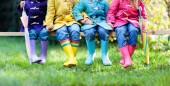 Gruppe von Kindern in Gummistiefel. Bunte Schuhe für Kinder. Jungen und Mädchen im Regenbogen Gummistiefeln und Dufflecoat. Regenbogen-Schuhwerk und Kleidung für Herbst oder Winter. Regenwetter Oberbekleidung und Mode
