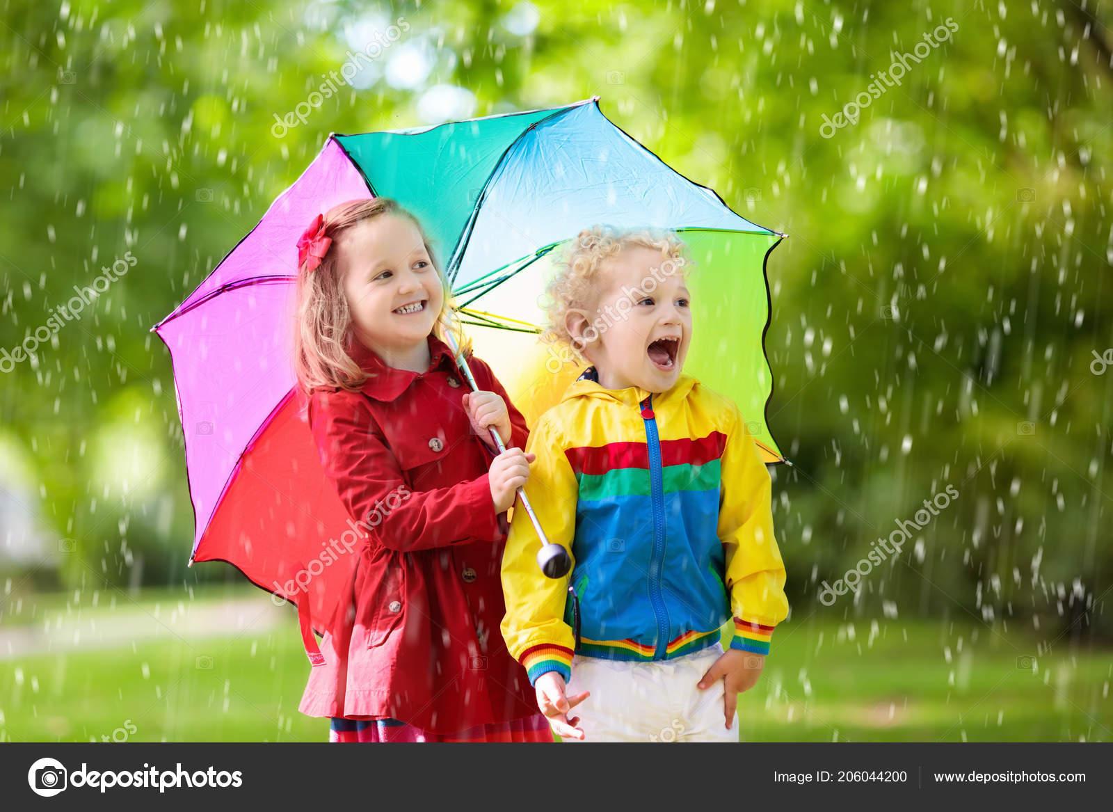 8dc535ed3db Malý chlapec a dívka hrají v deštivém létě parku. Děti s barevný duhový  deštník