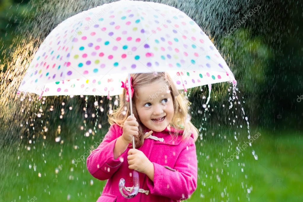 Little girl playing in rainy summer park. Child with colorful rainbow umbrella, pink coat walking in the rain. Kid having fun in autumn shower. Outdoor activity by any weathe