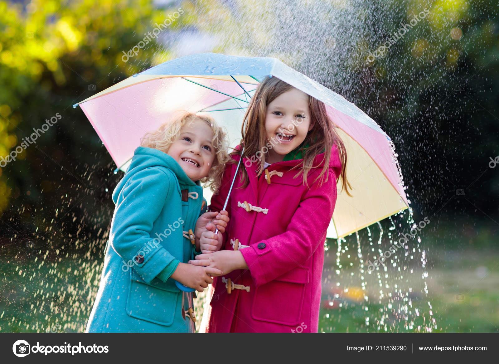 a3db923b370 Děti s Barevný deštník v podzimní déšť sprcha. Malý chlapec a dívka v teplá  vlněná látka kabát hrát v parku deštivé počasí. Na podzim venkovní zábava  pro ...