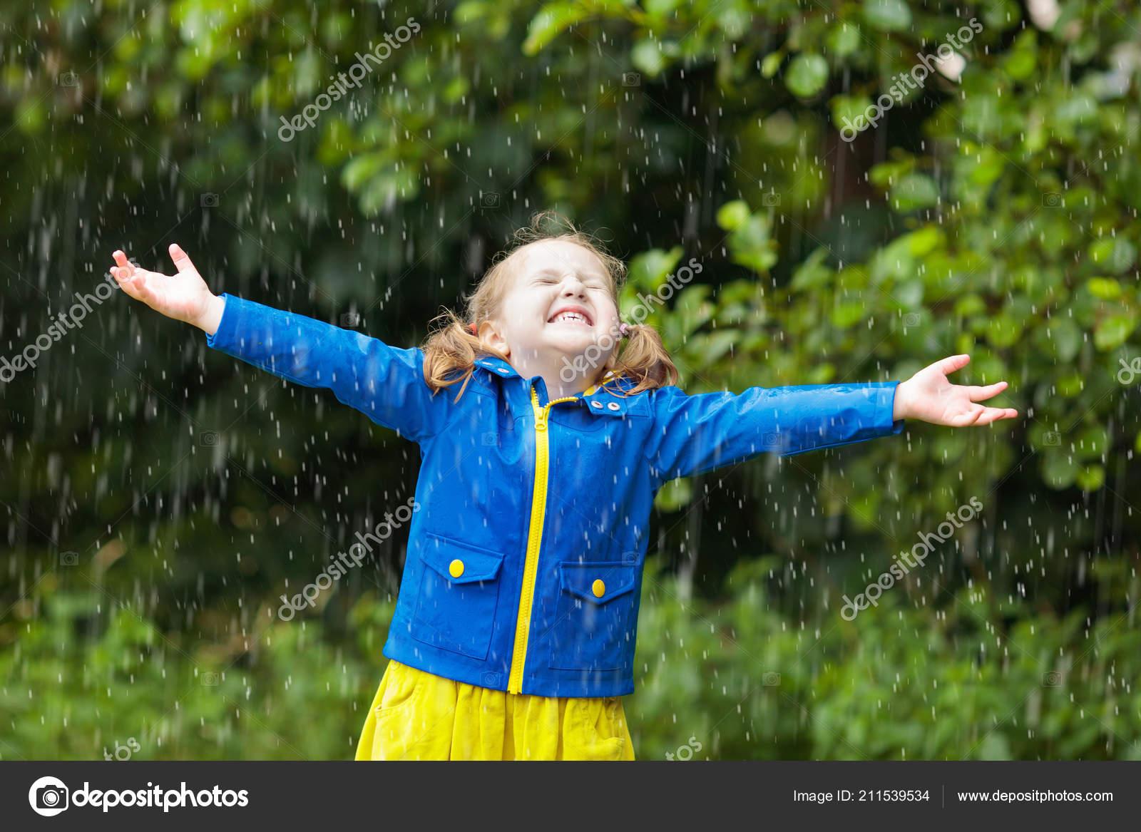 14ad817fff4 Malá holčička hraje v deštivé letní park. Dítě s barevný duhový deštník