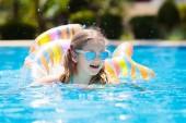 Fotografie Dítě s nafukovací hračka prsten plavat v bazénu. Malá holčička, naučit se plavat a potápět v venkovní bazén tropický resort. Plavání s dětmi. Zdravé sportovní aktivity pro děti. Vodní radovánky
