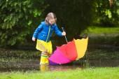 Fotografie Kleines Mädchen im regensommer Park spielen. Kind mit regenbogenfarbenen Regenschirm, blauen Mantel in schlammigen Pfütze springen, Wandern in den Regen. Kind mit Spaß im Herbst Dusche. Outdoor-Aktivitäten bei jedem Wetter