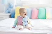 Fotografie Chlapeček v bílé ložnici. Novorozené dítě v posteli s pastelově barevných polštářů. Školka pro děti. Textil, polštáře a lůžkoviny pro děti. Rodinný den doma. Nové narozený dítě bříško čas s hračka medvěd