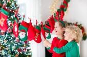 Kinder öffnen Weihnachtsgeschenke. Kind auf der Suche nach Süßigkeiten und Geschenke im Adventskalender am Wintermorgen. Geschmückter Weihnachtsbaum für Familie mit Kindern. Kleines Mädchen und Junge in Xmas Pyjamas.