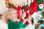 Fotografie Kinder Weihnachtsgeschenke zu öffnen. Kind auf der Suche nach Süßigkeiten und Geschenke im Adventskalender an Wintermorgen. Weihnachtsbaum für Familie mit Kindern eingerichtet. Kleiner Junge in Xmas Pyjamas
