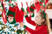 Kinder öffnen Weihnachtsgeschenke. Kinder auf der Suche nach Süßigkeiten und Geschenken im Adventskalender am Wintermorgen. geschmückter Weihnachtsbaum für Familie mit Kindern. kleines Mädchen im Weihnachtsschlafanzug.