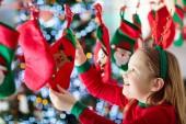 Kinder öffnen Weihnachtsgeschenke. Kind auf der Suche nach Süßigkeiten und Geschenke im Adventskalender am Wintermorgen. Geschmückter Weihnachtsbaum für Familie mit Kindern. Kleines Mädchen in Xmas pyjamas.