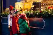 Kinder shoppen an einem verschneiten Wintertag auf dem traditionellen Weihnachtsmarkt in Deutschland. Kinder kaufen Waffeln, Süßigkeiten, Gebäck und Lebkuchen in fairen Konditoreien. Jungen und Mädchen wählen Süßigkeiten in Weihnachtsbäckerei.