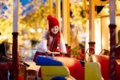 Fotografie Kinder am Weihnachtsmarkt. Kind am traditionellen Xmas Straßenmarkt in Deutschland. Winter-outdoor-Spaß. Kleines Mädchen im Karussell-Pferd im Outdoor-Freizeitpark im Winter Mütze Ferienzeit