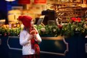Fotografie Kinder shoppen an einem verschneiten Wintertag auf dem traditionellen Weihnachtsmarkt in Deutschland. Kinder kaufen Waffeln, Süßigkeiten, Gebäck und Lebkuchen in fairen Konditoreien. kleines Mädchen wählt Süßigkeiten in der Weihnachtsbäckerei.