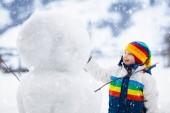 Fotografia Pupazzo di neve bambino edificio. Bambini costruire luomo di neve. Ragazzino che gioca allaperto il giorno di inverno nevoso. Divertimento della famiglia allaperto su vacanze di Natale. Palle di neve piccolo ragazzo gioco di volo. Ragazzo attivo di abbigliamento invernale
