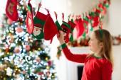 Fotografie Kinder öffnen Weihnachtsgeschenke. Kinder auf der Suche nach Süßigkeiten und Geschenken im Adventskalender am Wintermorgen. geschmückter Weihnachtsbaum für Familie mit Kindern. kleines Mädchen im Weihnachtsschlafanzug.