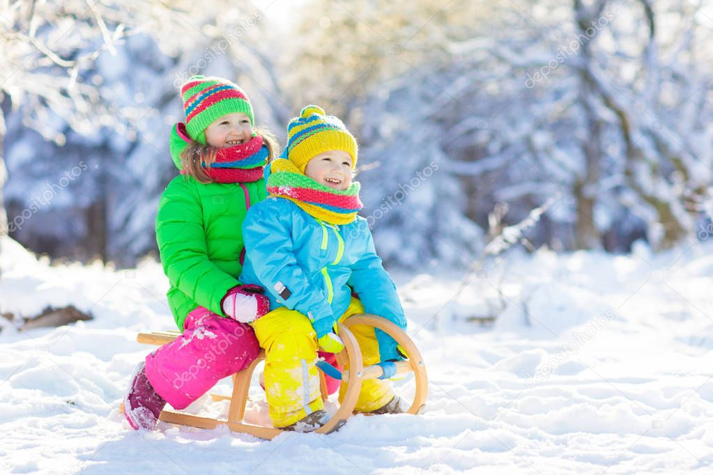 Little girl and boy enjoying sleigh ride. Child sledding. Toddler kid riding a sledge. Children play outdoors in snow. Kids sled in snowy park in winter. Outdoor fun for family Christmas vacation.