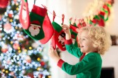 Kinder öffnen Weihnachtsgeschenke. Kind auf der Suche nach Süßigkeiten und Geschenke im Adventskalender am Wintermorgen. Geschmückter Weihnachtsbaum für Familie mit Kindern. Kleiner Junge in Xmas pyjamas.