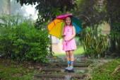 Fotografie Kinder spielen im Regen. Kinder mit Regenschirm und Regen Boots spielen im Freien bei starkem Regen. Kleines Mädchen in schlammigen Pfütze springen. Kinderspaß mit regnerischen Herbstwetter. Kind im tropischen Sturm laufen