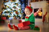 Kind am Weihnachtsbaum zu Hause vorhanden. Kid im Elf-Kostüm mit Weihnachten Geschenke und Spielzeug. Kleine Baby-Junge mit Geschenk-Box und Süßigkeiten am Kamin. Familie Winterurlaub zu feiern. Heimtextilien