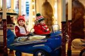 Fotografie Kinder am Weihnachtsmarkt. Kind am traditionellen Xmas Straßenmarkt in Deutschland. Winter-outdoor-Spaß. Kleine Mädchen und jungen in Strickmütze Reiten Karussell im Outdoor-Freizeitpark im winter Ferienzeit