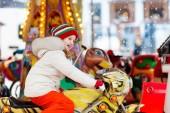 Kinder auf dem Weihnachtsmarkt. Kind beim traditionellen Straßenweihnachtsmarkt in Deutschland. Winter-Outdoor-Spaß. Kleines Mädchen mit Strickmütze reitet Karussell in Outdoor-Freizeitpark in der Winterferienzeit.
