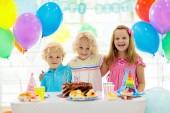 Děti narozeninovou oslavu. Dítě, foukání svíčky na dort barevné. Zdobené domov s duhové vlajky bannery, balóny. Farma zvířat téma oslav. Malý chlapec slaví narozeniny. Strana potravin