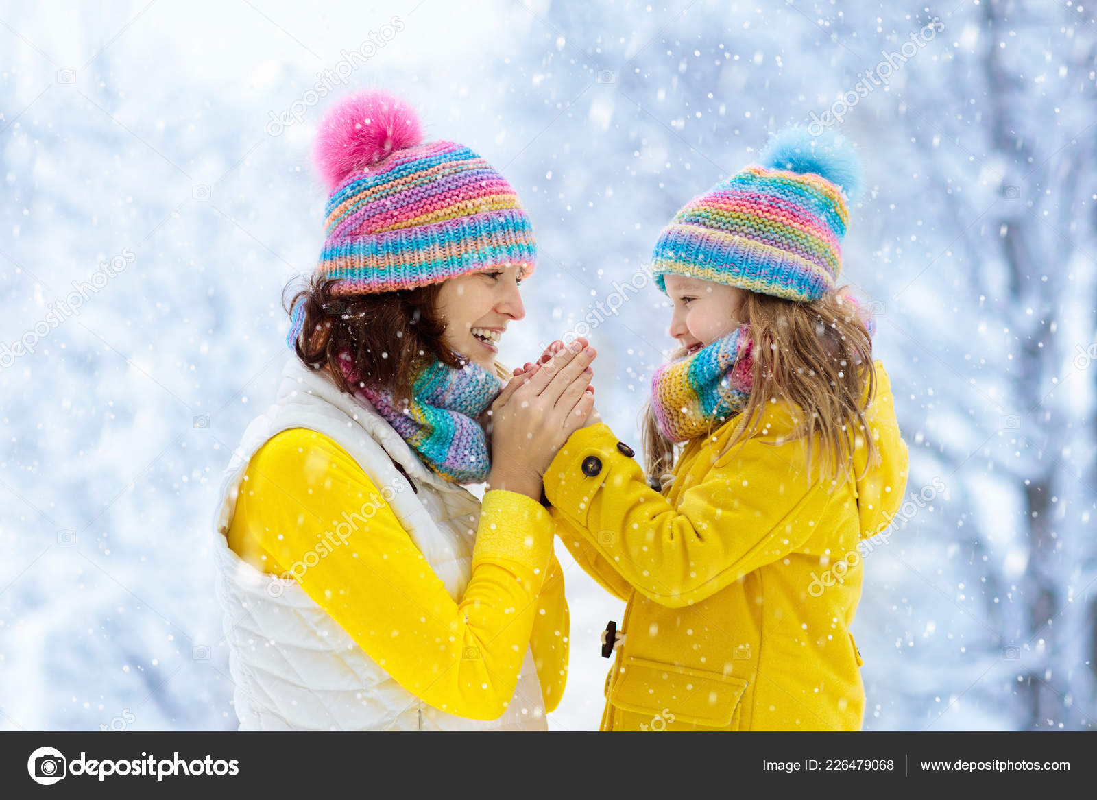 Mother and child in knitted winter hats play in snow on family Christmas  vacation. Handmade wool hat and scarf for mom and kid. Knitting for kids. ff89d556da57