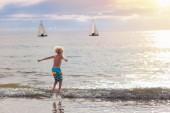 Kind spielt am Strand. Kind bei Sonnenuntergang Meer.